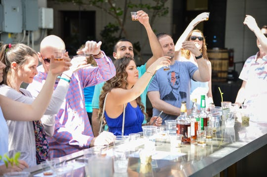 Sour Mash Tour participants check out the color of their bourbon at a tasting event.