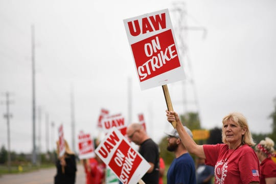 UAW members, including LeAnn Cramer, right, picket outside of the General Motors Lansing Delta Township plant early Monday morning, Sept. 16, 2019, the first day of a nationwide strike against GM.   Cramer has worked at GM for 24 years.