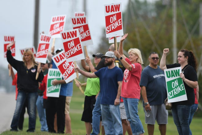 UAW members picket outside of the General Motors Lansing Delta Township plant early Monday morning, Sept. 16, 2019, the first day of a nationwide strike against GM.   Cramer has worked at GM for 24 years.