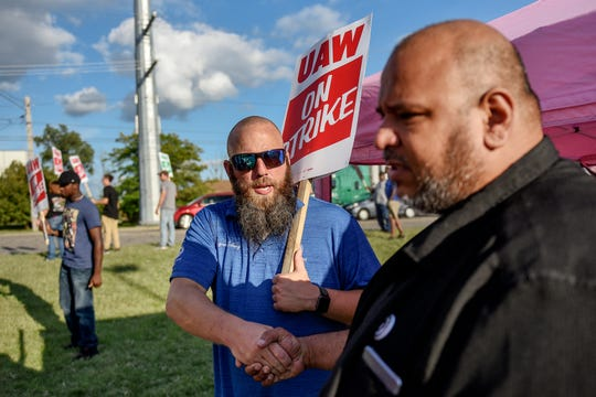 UAW member Ryan Eding, left, shakes Geronimo Lerma's hand after Lerma handed out sandwiches and other food to UAW members on strike outside the GM Central Distribution Center on Monday, Sept. 16, 2019, in Lansing. Lerma, a former UAW member, founded the nonprofit Footprints of Michigan.