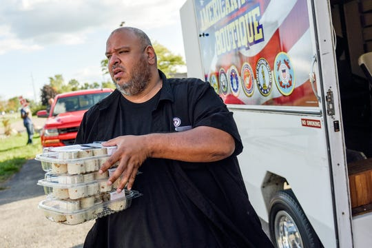 Geronimo Lerma, a former UAW member who founded the nonprofit Footprints of Michigan, takes trays of food to UAW members on strike outside the GM Central Distribution Center on Monday, Sept. 16, 2019, in Lansing.