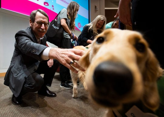 President and CEO of St. Jude Children's Research Hospital James R. Downing, M.D., reaches out to pet canine pal Huckleberry at the Marlo Thomas Center in Memphis on Monday, Sept. 16, 2019.