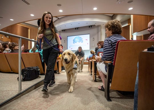 Child Life Specialist Brittany Reed and canine pal Puggle walk together at the Marlo Thomas Center in Memphis on Monday, Sept. 16, 2019.