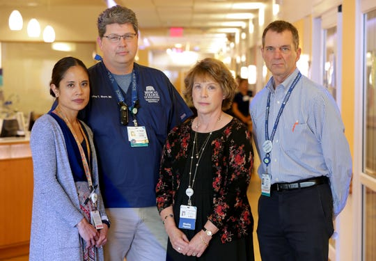 Four Children's Hospital doctors, from left, Louella Amos, a pulmonologist; Micheal Meyer, medical director of the Pediatric Intensive Care Unit; Lynn D'Andrea, medical director of pulmonary services; and Michael Gutzeit, chief medical officer, take time out Monday in the Pediatric Intensive Care Unit.
