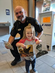 3-year old Lainie Stephens gives police chief Peter Hoell $754 to go towards another police canine dog Sept. 12.  Lainie and her family were inspired to the cause because her family had a German Shepherd, and her great -grandfather was a police officer and also had a German Shepherd.
