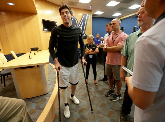 Christian Yelich leaves the interview room on crutches Monday after he spoke publicly for the first time since suffering a broken right kneecap.