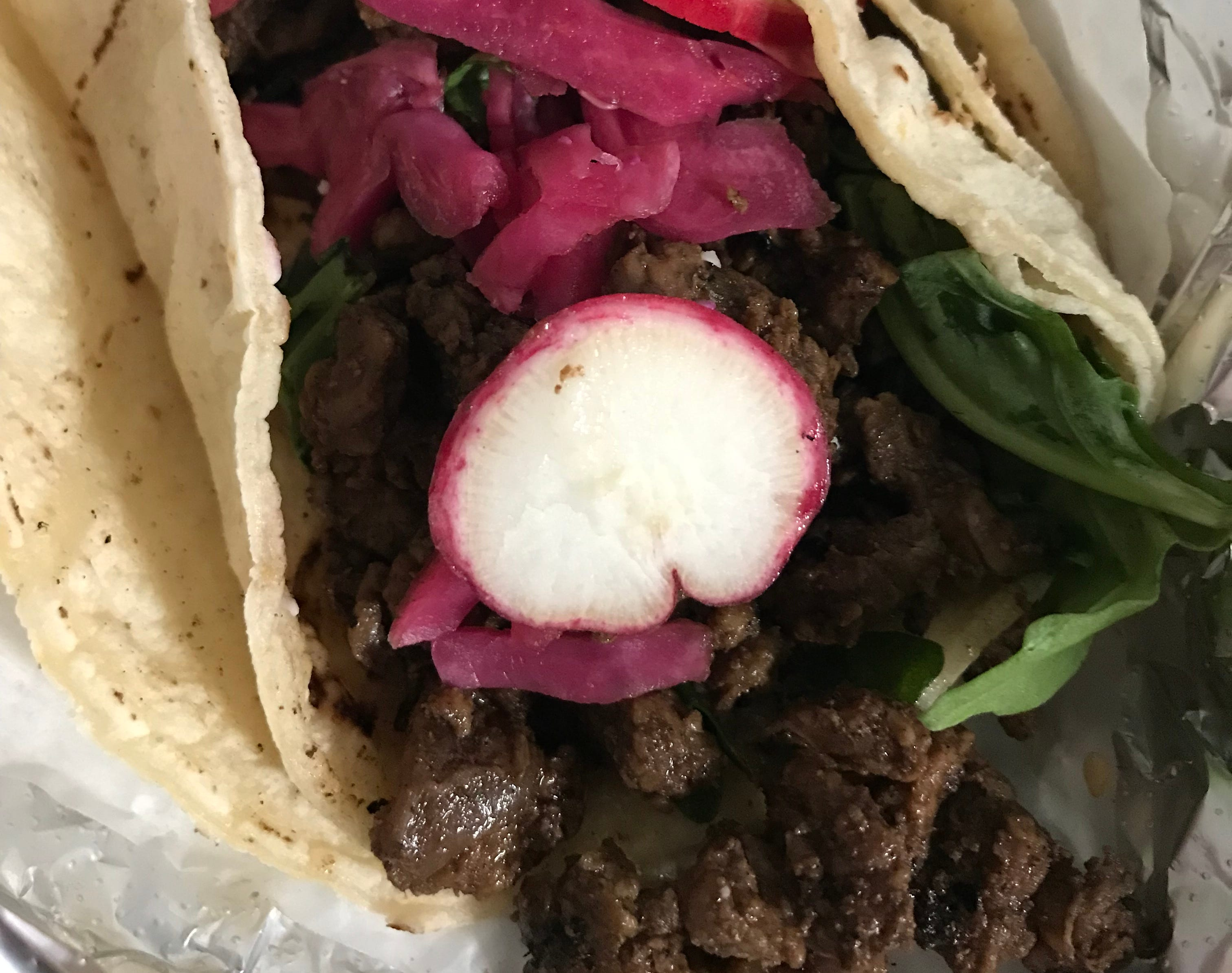 """One of Taco Moto's """"O.G."""" tacos is filled with braised beef. The taco truck is parked year-round outside Boone & Crockett bar, 818 S. Water St. in the Harbor District."""