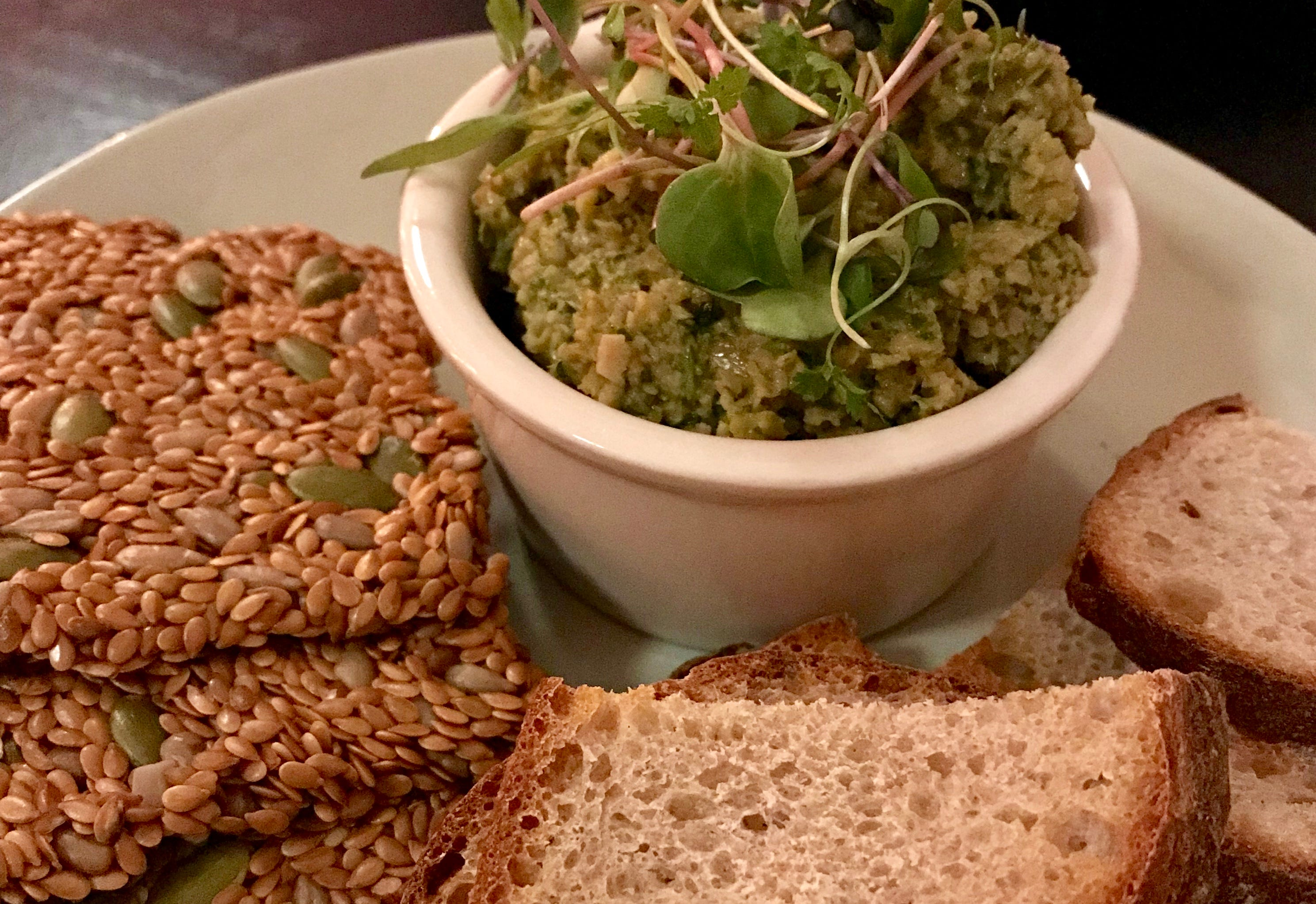 Olive tapenade with seed crackers and crusty bread is an example of the shareable plates on the changing, vegan menu at Strange Town, 2101 N. Prospect Ave.