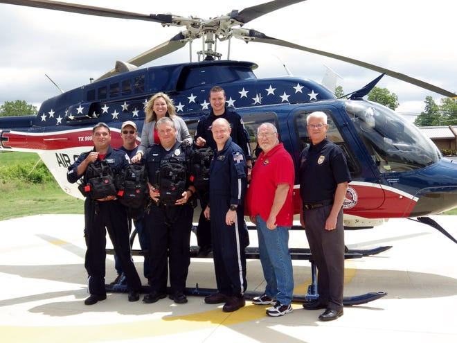 """Officers from the Mountain Home Police Department are shown holding """"go bags"""" with representatives of Air Evac 12 and the Mountain Home Citizens Police Academy Alumni Association. Air Evac and the MHCPAAA each donated to provide materials and financial assistance for the """"go bags."""""""