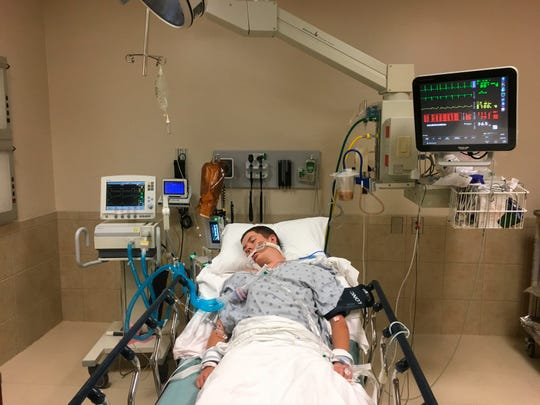 This May 2018, photo provided by Joseph Jenkins shows his son, Jay, in the emergency room of the Lexington Medical Center in Lexington, S.C. Jay Jenkins suffered acute respiratory failure and drifted into a coma, according to his medical records, after he says he vaped a product labeled as a smokable form of the cannabis extract CBD. Lab testing commissioned as part of an Associated Press investigation into CBD vapes showed the cartridge that Jenkins says he ingested contained a synthetic marijuana compound blamed for at least 11 deaths in Europe.