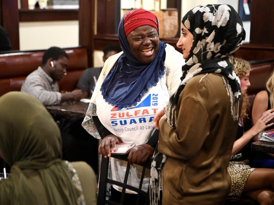Zulfat Suara speaks to Kasar Abdulla during her election night watch party at House of Kabob Thursday, Aug. 1, 2019, in Nashville, Tenn.