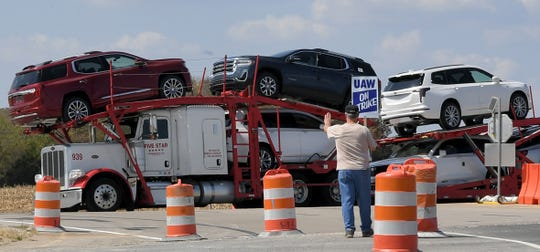 GM worker James Hatfield waves to a truck full of new cars as it leaves GM plant in Spring Hill, Tenn. on Monday, Sept. 16, 2019. General Motors workers started striking outside the GM plant in Spring Hill, Tenn. at midnight on Monday, Sept. 16, 2019.