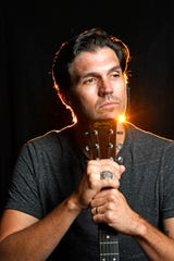 Former star baseball pitcher Barry Zito, wearing his 2010 World Series ring, poses with his acoustic guitar in his Nashville home on Sept. 13, where he has built a professional recording studio.