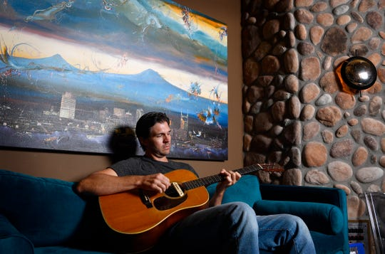 Former superstar baseball pitcher Barry Zito strums his guitar on a couch in the recording studio he built in his Nashville house on Sept. 13.