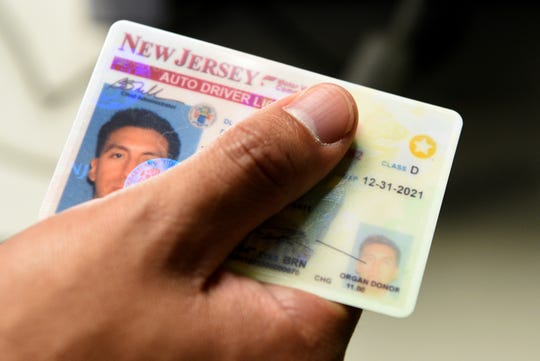 A New Jersey driver holds a Real ID card.