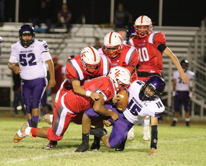 Loving's defense gang-tackles Mescalero Apache quarterback Duncan Balatche during Loving's homecoming game on Sept. 13, 2019. Loving won, 47-0. Loving has gone 2-0 since switching its offensvie game plan with two 47-plus point wins and allowed zero points.