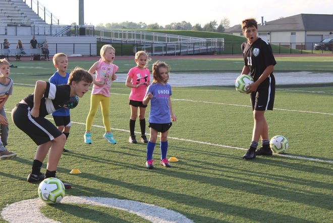 Members of the South Lyon East soccer team help youngsters with drills at their team camp last week.