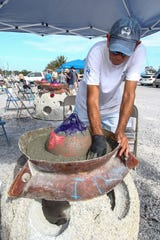 Robbie Duke sets wet concrete on top of an eternal reef Friday so family members and friends can permanently place mementos, handprints and more before the reef is placed into water about 2 miles offshore.