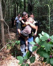 Santa Rosa County Sheriff's Office Deputy Robert Lenzo carries Aedric Arnold, 3, out of the woods after he went missing Sunday.