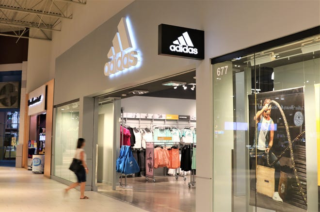 A woman walks into the Adidas Clearance Store at Arizona Mills in Tempe on Friday, Sept. 13