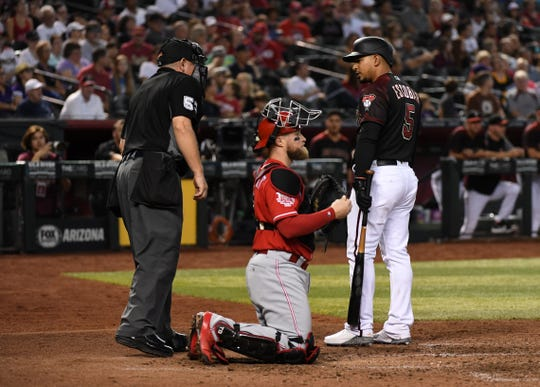 Eduardo Escobar #5 of the Arizona Diamondbacks argues with home plate umpire Greg Gibson #53 after being called out on strikes during the sixth inning as Tucker Barnhart #16 of the Cincinnati Reds listens in at Chase Field on September 15, 2019 in Phoenix, Arizona.