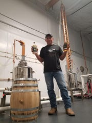 Wild Hare Distillery co-owner Jim Matz holds a couple of bottles filled with agave spirits distilled in his Tempe facility.