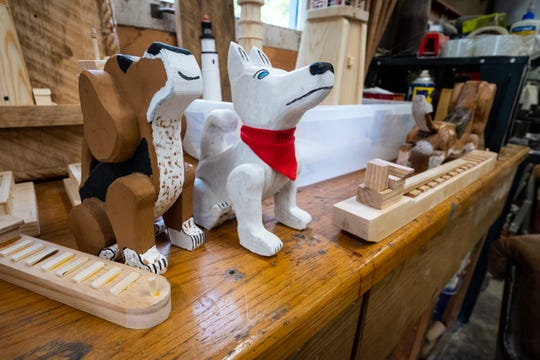 Two wooden dogs stand on a shelf in Mike Britz's St. Clair workshop. Britz said the dogs, which are modeled and painted to look like his own, were some of his first wooden creations.