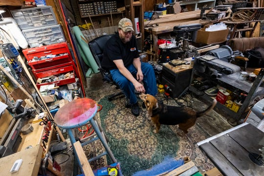 Mike Britz reaches down for his 10-year-old Beagle Boom Boom in his St. Clair workshop Friday, Sept. 13, 2019. Britz says Boom Boom is the CEO of his woodworking shop.