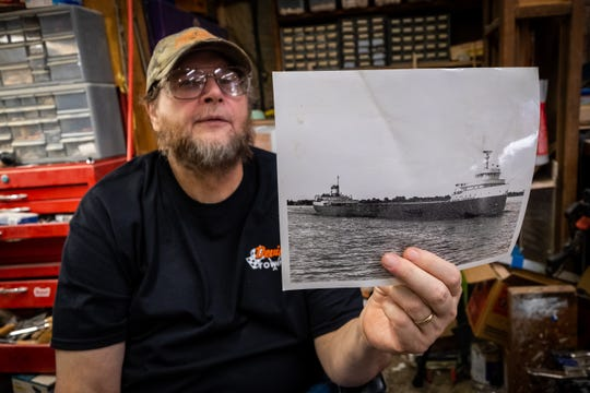 Mike Britz holds a photo of the Edmund Fitzgerald he uses for reference when he builds wooden models of the ship.