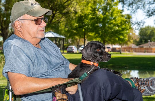 John Perri, of Carson City, relaxes in the shade with Buster, 9 , a mini Dachshund and Black Lab mix he adopted from a rescue in Reno.