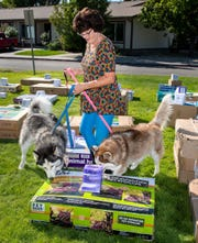 Debbie McGhauey, from Yerington, and her dogs Sky and Blue, looks at items donated by Chewy and given away at Pet Lovers Day.