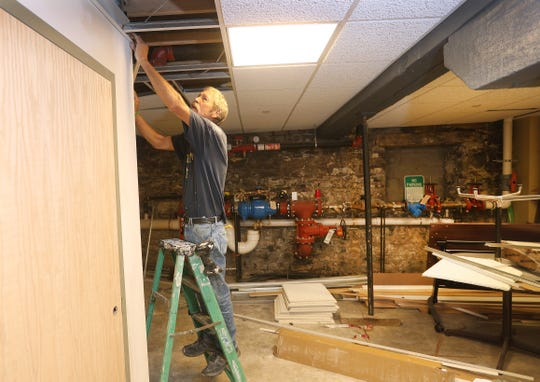 Construction worker George Lampman adding walls and ceilings inside Bivona Child Advocacy Center that will create more office space for its employees.