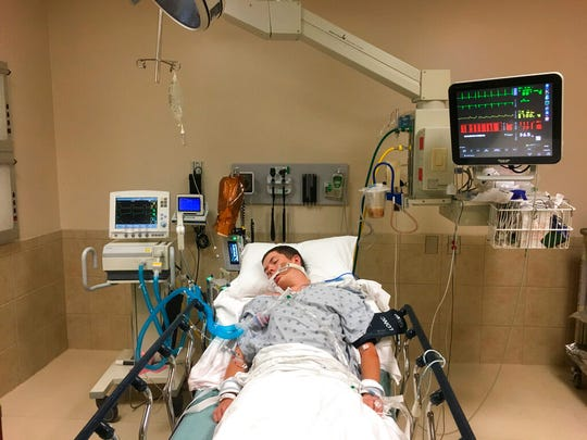 This May 2018, photo provided by Joseph Jenkins shows his son, Jay, in the emergency room of the Lexington Medical Center in Lexington, S.C. Jay Jenkins suffered acute respiratory failure and drifted into a coma, according to his medical records, after he says he vaped a product labeled as a smokable form of the cannabis extract CBD. Lab testing commissioned as part of an Associated Press investigation into CBD vapes showed the cartridge that Jenkins says he puffed contained a synthetic marijuana compound blamed for at least 11 deaths in Europe.  (Joseph Jenkins via AP)