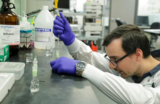 Pierce Prozy prepares a CBD vape oil test sample at Flora Research Laboratories in Grants Pass, Ore., on July 19, 2019. The Associated Press commissioned the lab to test 30 vape products marketed as delivering the cannabis extract CBD. The testing was part of an investigation that shows some people are taking advantage of gaps in federal regulation and law enforcement to exploit booming demand for CBD by substituting cheap and illegal synthetic marijuana for natural CBD. (AP Photo/Ted Warren)