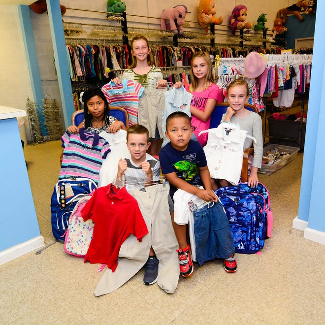 Jennifer, clockwise, from left, Emily, Samantha, Charlotte, Edwin and Billy display some of the clothing available at the Caring Children Clothing Children store in Stuart.