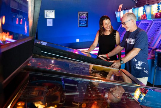 """""""I haven't played some of these games since college. It's a great thing to do for all ages. He brought our grandchildren here and everyone had fun,"""" said Donna Schultz of Stuart, who watches her husband, Chris, play the AC/DC pinball game at Play Money Pinball on Sunday, Sept. 15, 2019, in Stuart. The family friendly arcade, which opened last February, is the only retro arcade of its kind on the Treasure Coast with more than 30 pinball machines, old-school arcade games, air hockey, table shuffleboard and video game consoles. It costs $15 for unlimited play and $10 if you come in before 4 p.m. on weekdays. Visitors, including parents, grandparents and chaperones do not have to pay if they are not playing the games."""