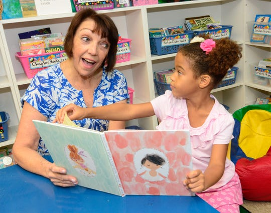 Maureen Bardi-Wegner, left, a retired banker, reads with Abby, 4, in the Caring Children Clothing Children store library.