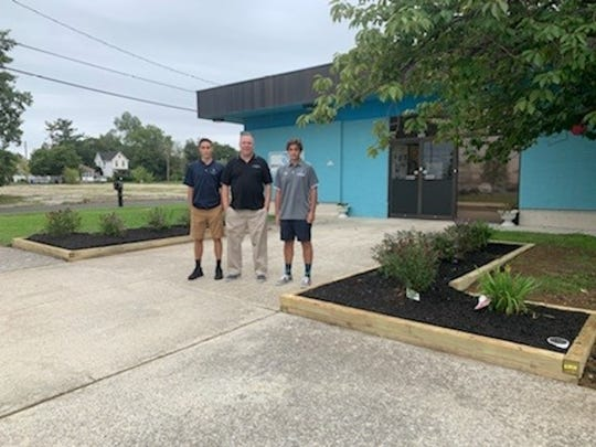 (From left) Cole Bennett, Chris Volker, director, Boys and Girls Club of Vineland,  and Anthony Cristelli, stand near a new entry walkway garden installed at the club's teen center in Vineland. Bennett and Cristelli, both of Vineland and students at St. Augustine College Preparatory School, installed the garden as part of their senior Caritas Project.