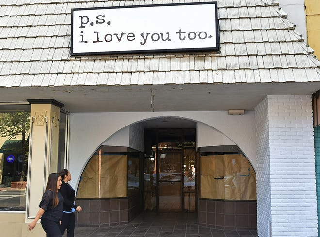 Pedestrians walking down Main Street glance at the shuttered storefront of boutique p.s. i love you too. on Sept. 9, 2019.