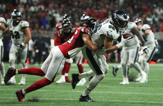 Atlanta Falcons cornerback Isaiah Oliver (26) tackles Philadelphia Eagles tight end Zach Ertz (86) after a catch in the fourth quarter against the at Mercedes-Benz Stadium.