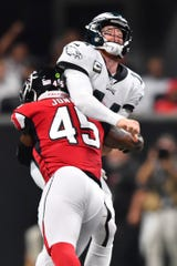 Atlanta Falcons linebacker Deion Jones (45) hits Philadelphia Eagles quarterback Carson Wentz (11) during the first half of an NFL football game, Sunday, Sept. 15, 2019, in Atlanta. (AP Photo/John Amis)