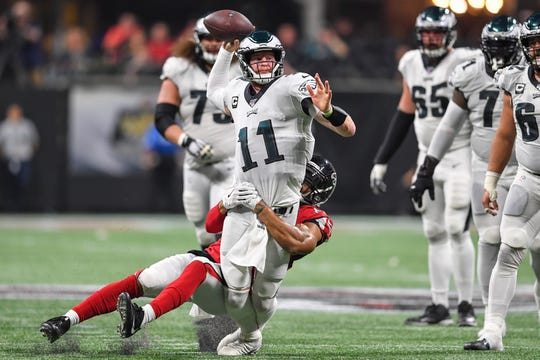 Philadelphia Eagles quarterback Carson Wentz (11) passes while being tackled by Atlanta Falcons linebacker Vic Beasley (44) during the fourth quarter at Mercedes-Benz Stadium.