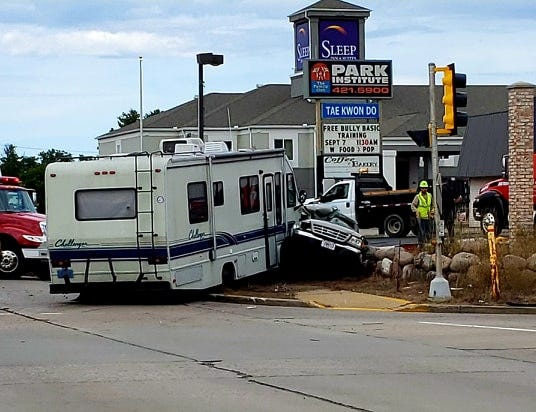 A pickup and recreational vehicle sit at the intersection of Eighth Street and Kuhn Avenue Saturday following a crash that sent both drivers to hospitals