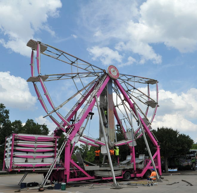 Construction crews work to build the Ferris wheel which represents the coming of the Texas-Oklahoma Fair to the Wichita Falls Multipurpose Event Center.