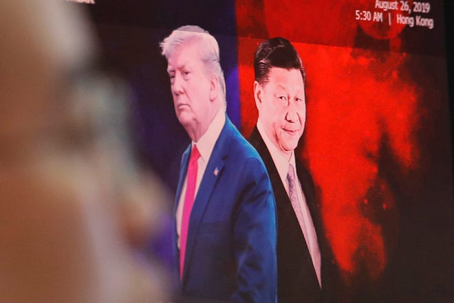 A computer screen shows images of Chinese President Xi Jinping, right, and U.S. President Donald Trump as a currency trader works at the foreign exchange dealing room of the KEB Hana Bank headquarters in Seoul, South Korea. China will lift punitive tariffs imposed on U.S. soybeans and pork in a trade war with Washington, a state news agency said Friday, Sept. 13, 2019, in a possible goodwill gesture ahead of negotiations.