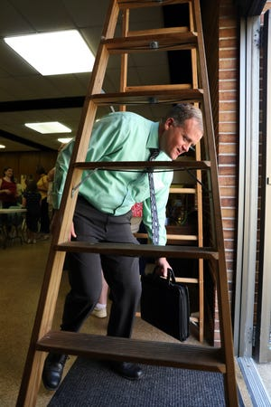 Kevin Pinson ducks under a ladder as he leaves the Friday the 13th meeting of the Zanesville Kiwanis.