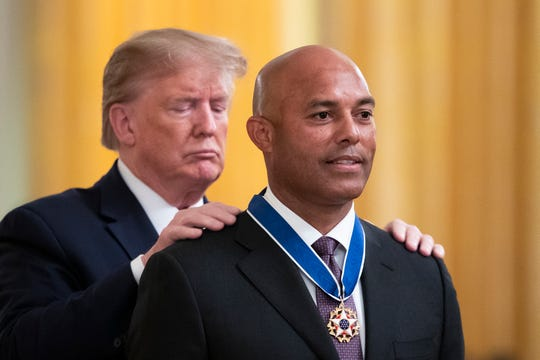 President Donald Trump presents the Presidential Medal of Freedom to former New York Yankees pitcher Mariano Rivera during a ceremony Monday in the East Room of the White House.
