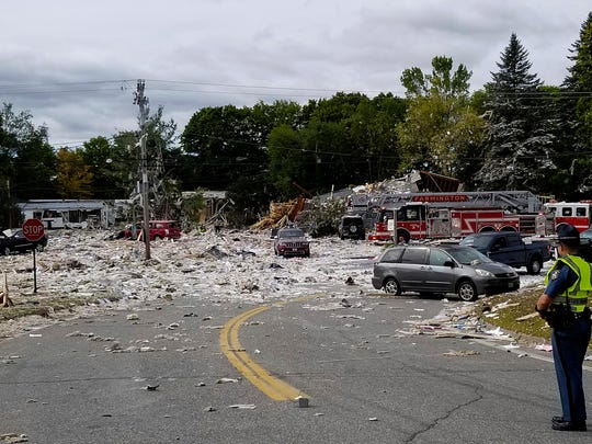 A police officer stands guard at the scene of a deadly propane explosion that leveled a new building in Farmington, Maine.