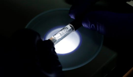 A Yolo! brand CBD vape oil cartridge is examined at Flora Research Laboratories in Grants Pass, Ore., on July 17, 2019. The Associated Press commissioned the lab to test that vape and 29 others as part of an investigation that shows a dark side to the booming industry selling the cannabis extract CBD. The Yolo cartridge and nine other samples contained synthetic marijuana, a dangerous street drug commonly known as K2 or spice.
