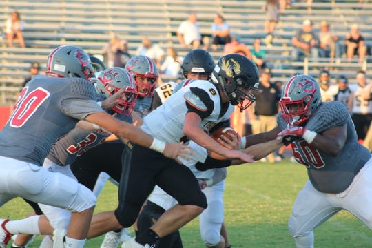 Crescent quarterback Landon Sauers takes the carry against several Mustang defenders.
